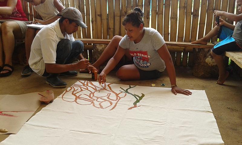 Los padres y madres de familia también se hicieron presentes. Les correspondió pintar las raíces como símbolo de origen bajo la metáfora del árbol comunitario: agarran y sostienen el árbol, adquieren los nutrientes de la tierra para dar fruto y seguir creciendo.