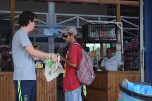 Estudiante y vecino de la comunidad conversan sobre el uso de las bolsas plásticas y los beneficios de las bolsas de tela.  Foto por: Roberto Puello Padilla.