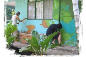 Estudiantes del TCU pintando murales en escuelas.