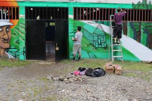 """Los artistas Mush y Kein de espaldas trabajando sobre la pared. A la izquierda está la imagen de perfil del líder comunitario """"don Roberto"""". Fotografía del Programa Kioscos Socio-ambientales."""